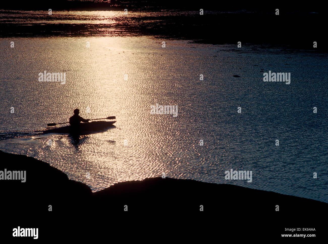 INUIT KAYAKER AT SUNSET, PANGNIRTUNG FIORD, BAFFIN ISLAND, NORTHWEST TERRITORIES, NUNAVUT, CANADA - Stock Image