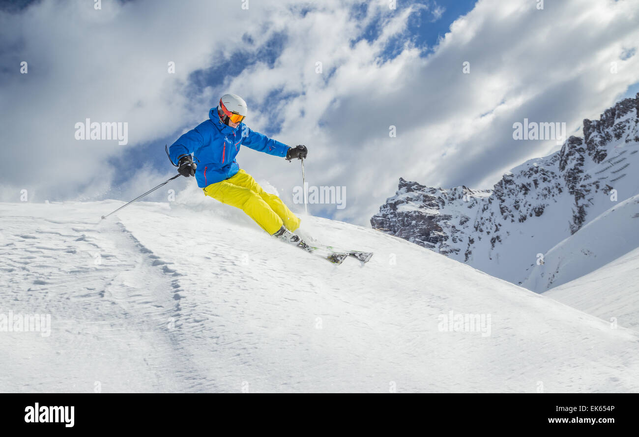 Skier skiing downhill in high mountains during sunny day. - Stock Image