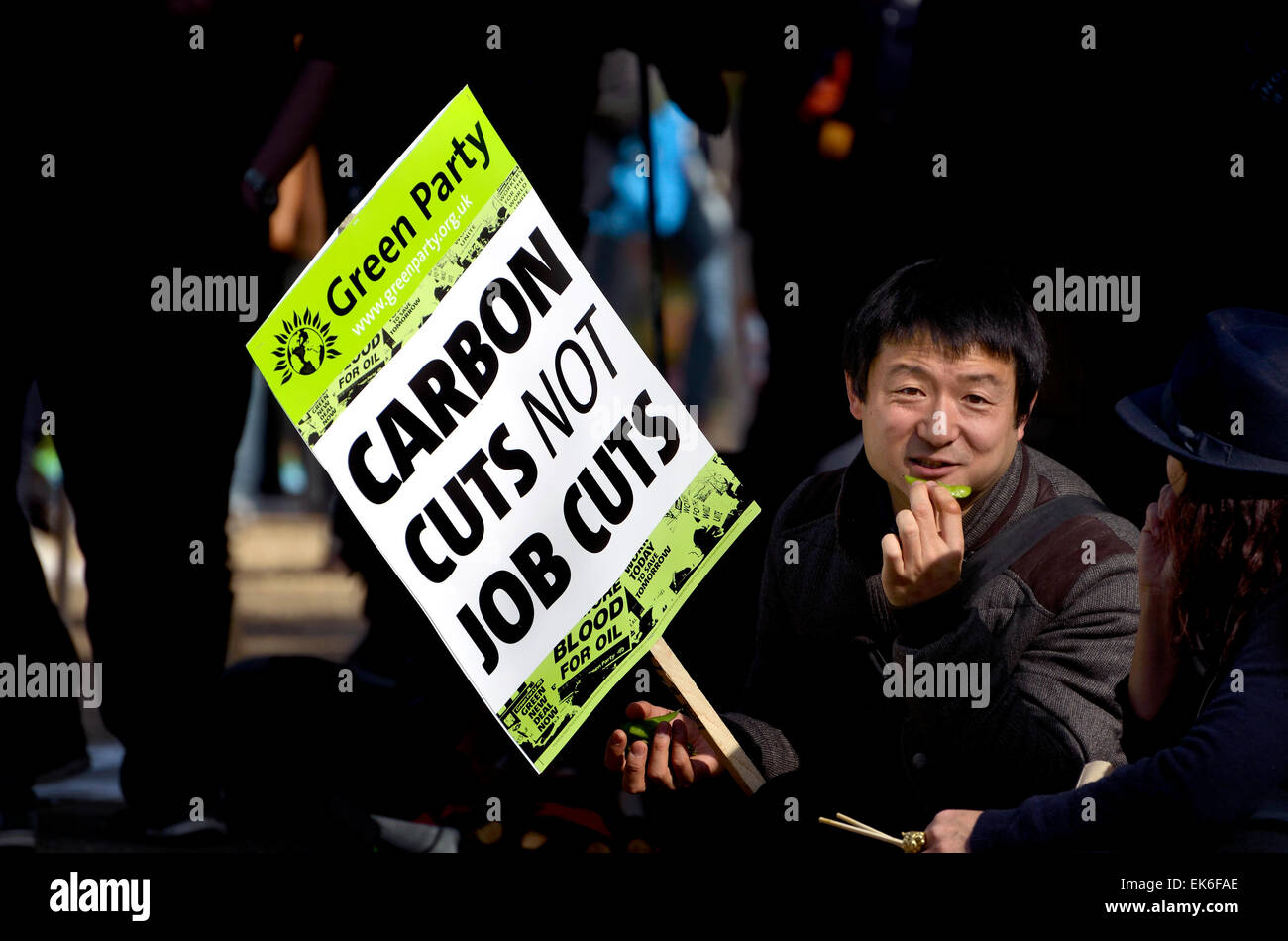 London, 7th March. Time To Act climate march through London to Parliament for a rally. Asian man holding Green Party - Stock Image