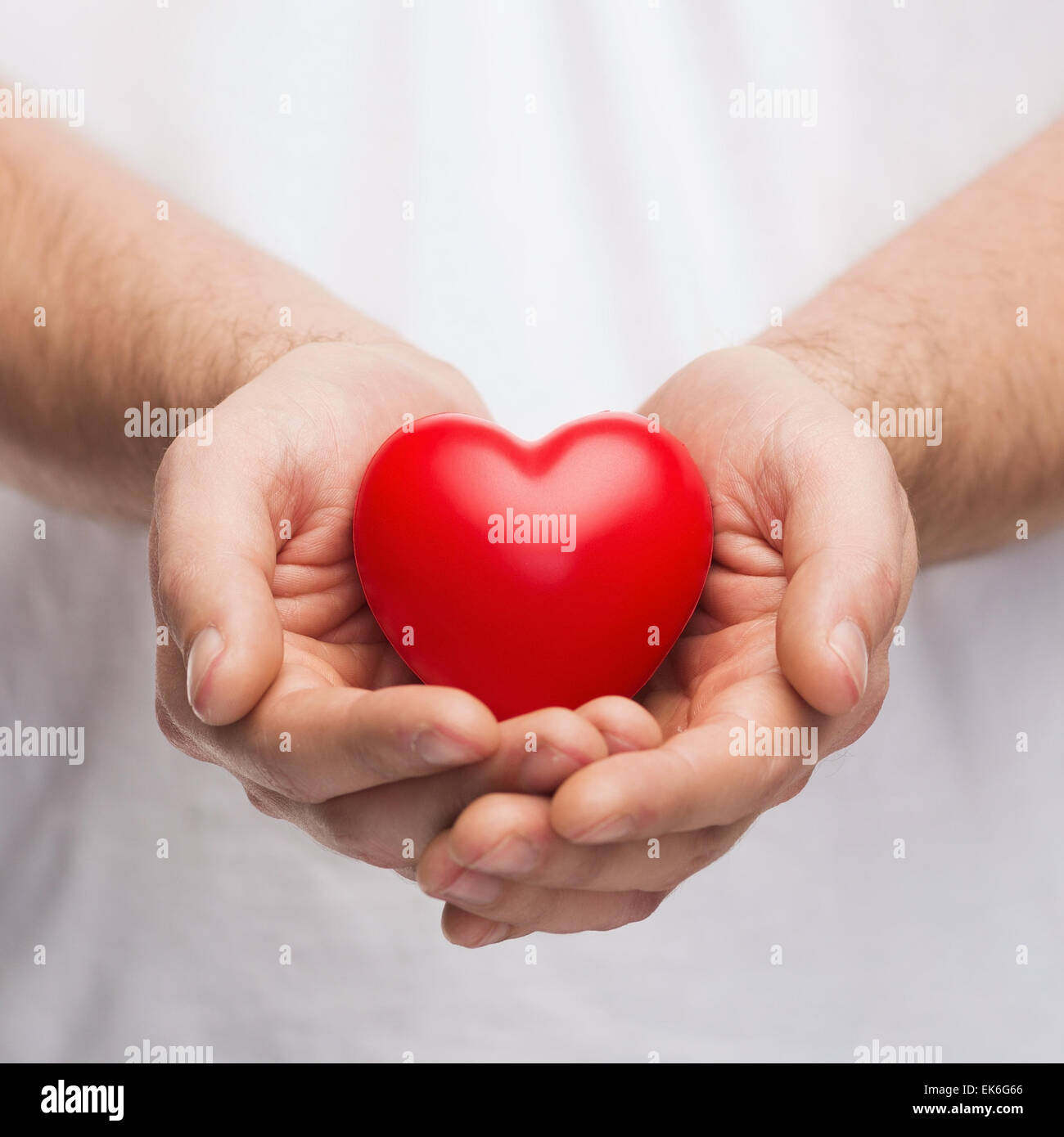 mans cupped hands showing red heart - Stock Image