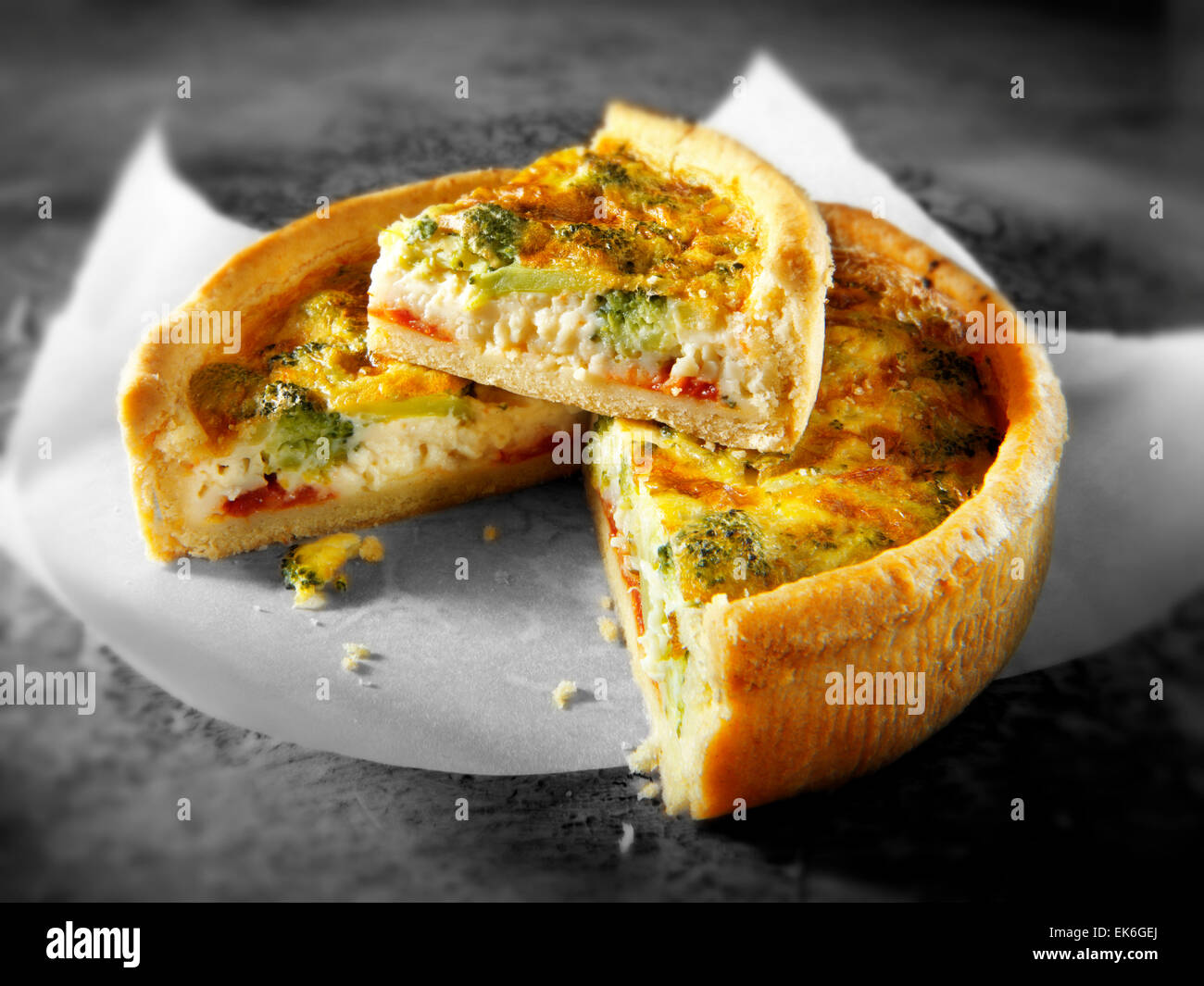 Whole cooked brocoli quiche with a slice out - Stock Image