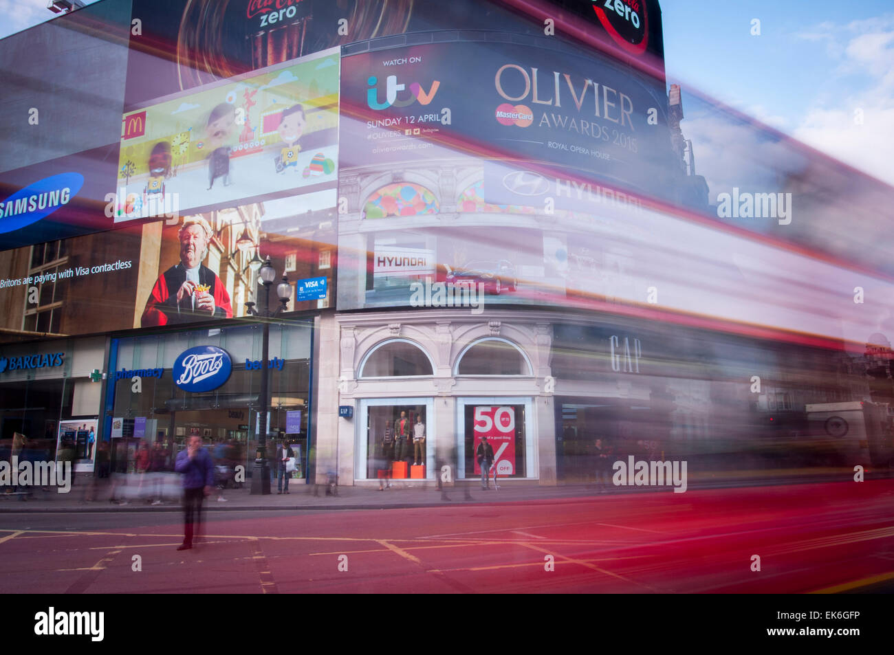 Piccadilly Circus with red London bus. - Stock Image