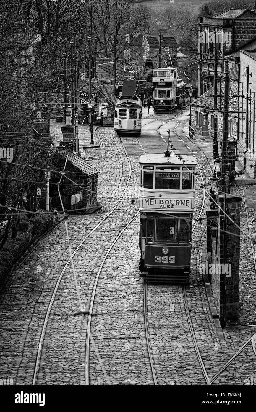 Monochrome: Tram 399 (served in Leeds in 1926) moves towards the village terminus where a driver enters Tram 345 - Stock Image
