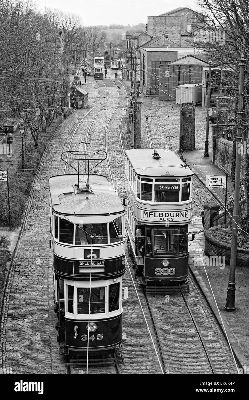 Black & White - A driver on the platform of Tram 399 (Leeds 1926) as Tram 345 (Leeds 1921) passes on its way - Stock Image