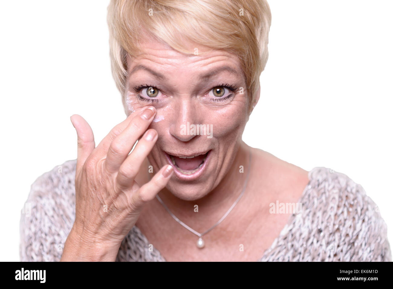 Middle-aged attractive blond woman applying anti-aging cream to the wrinkles around her eyes in an effort to combat - Stock Image