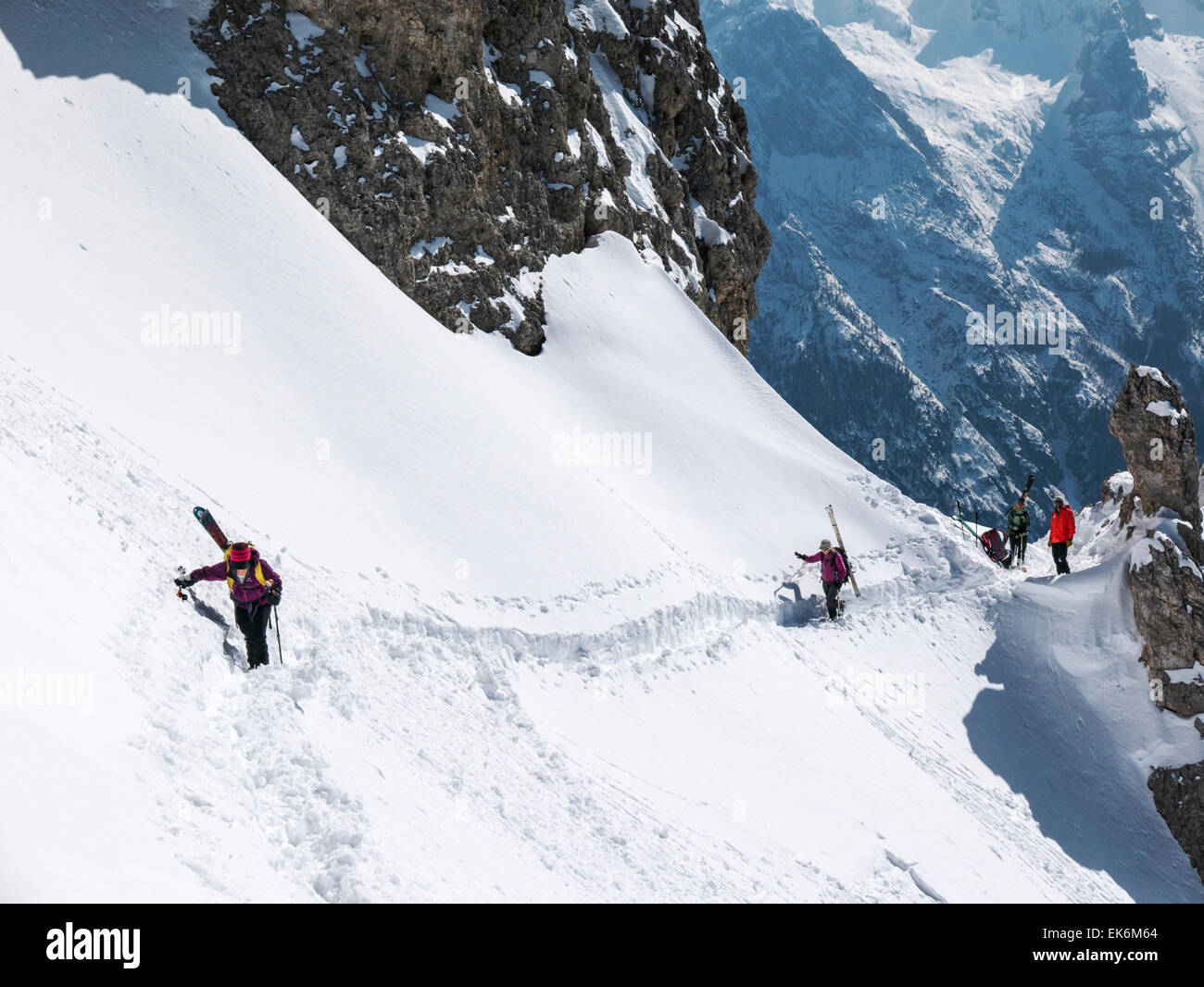 Backcountry skiers traversing steep slope, northeast of Cortina, Dolomite Mountains, Alps, Italy - Stock Image