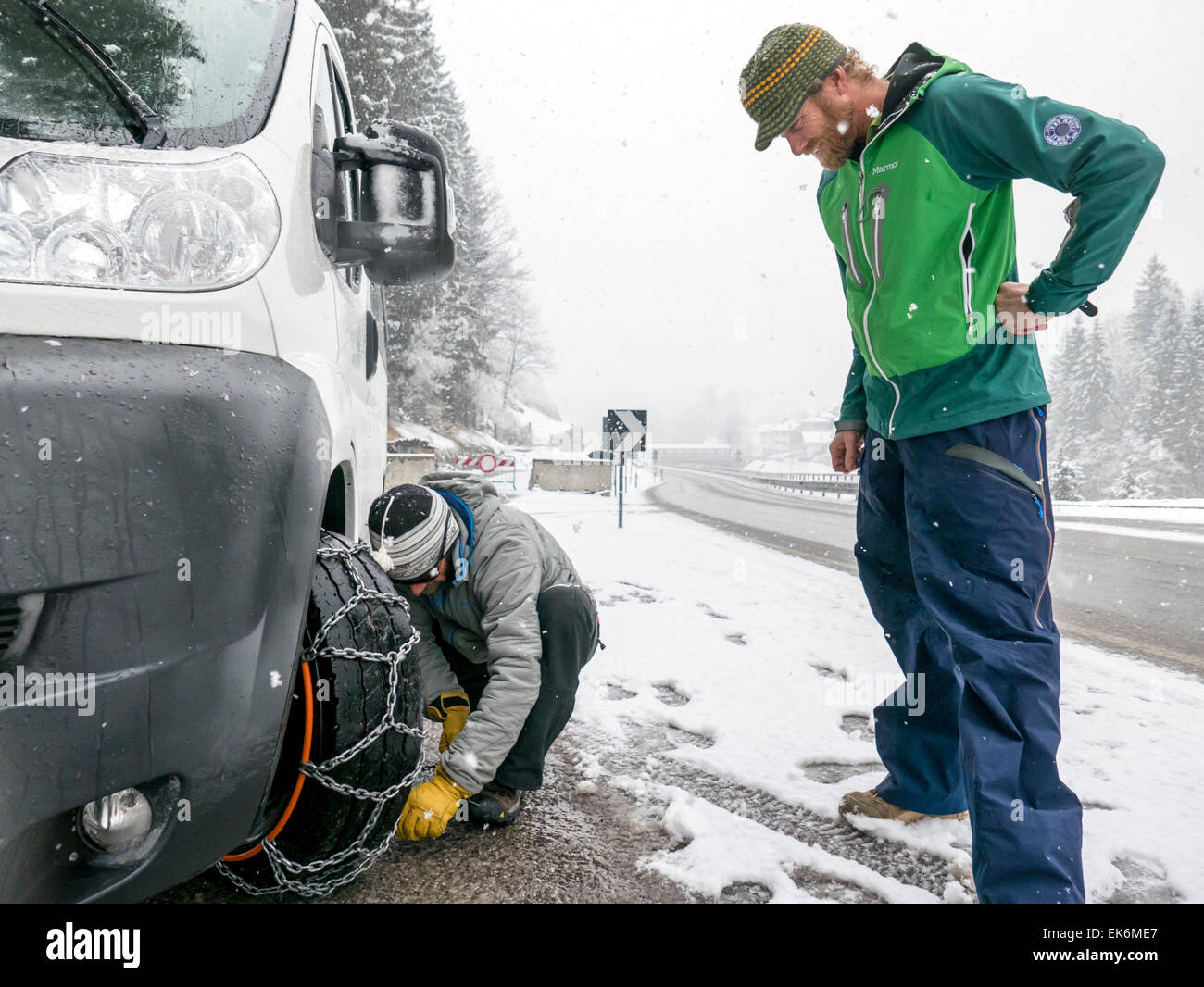 American skiers putting chains on a rental van, Dolomite Mountains, northern Italy - Stock Image