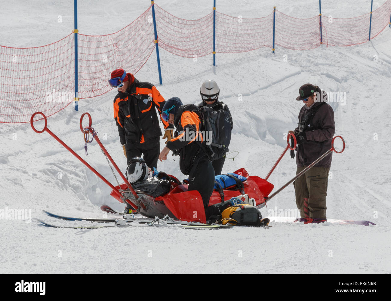 An injured skier on a rescue sledge after being helped by the ski patrol in the alps after a skiing  fall on a ski - Stock Image
