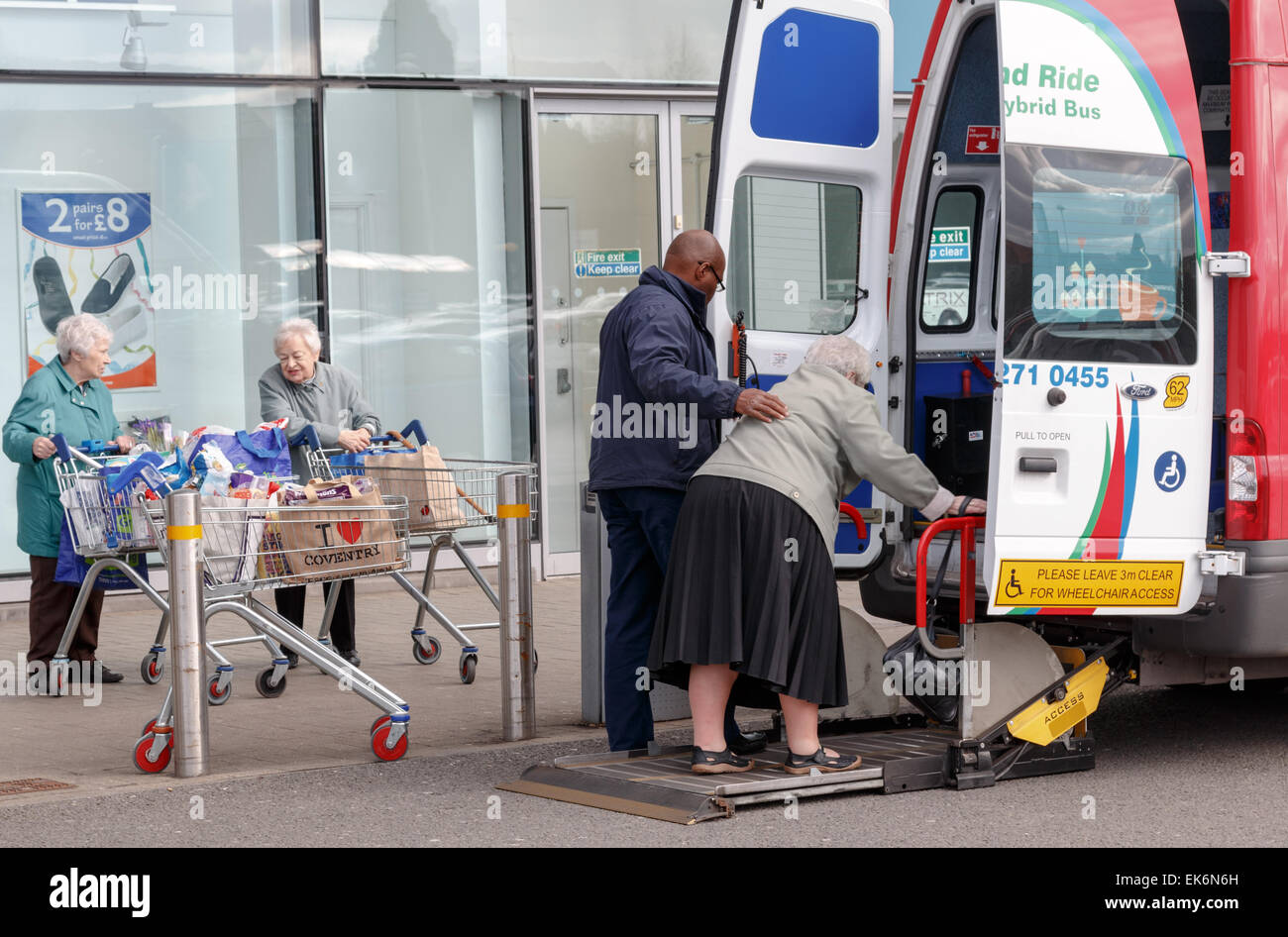 Elderly woman being helped aboard a lift at the rear of a minibus especially designed for disabled access.  In Coventry. - Stock Image