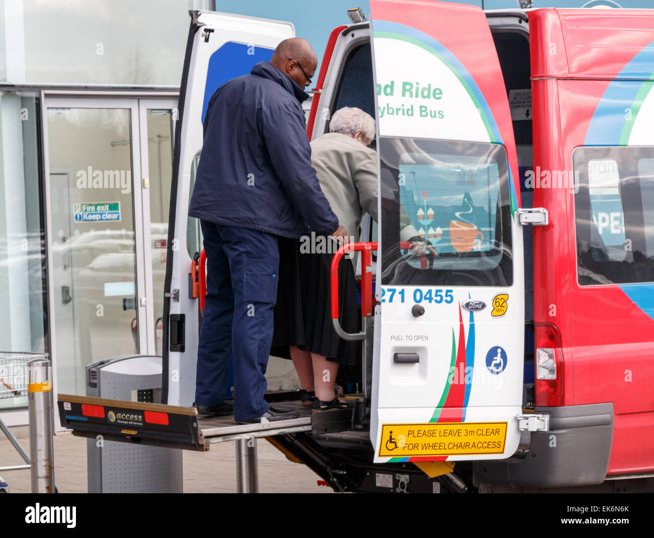 An elderly lady on a lift at the rear of a disabled park and ride hybrid minibus at a shopping centre in Coventry. Stock Photo