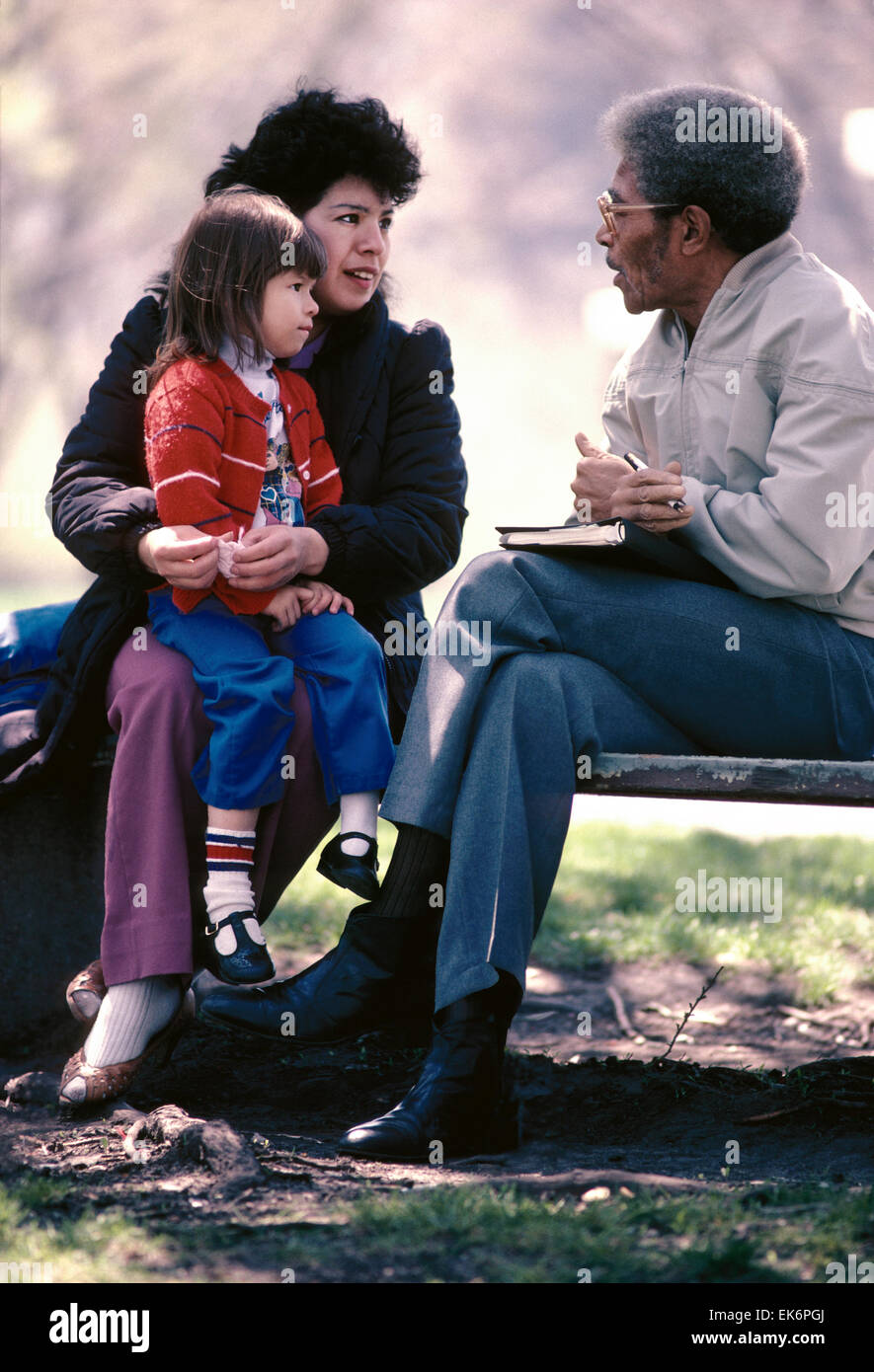 Male African American social worker counsels single Hispanic mother & child; Chicago Illinois Dept of Public - Stock Image