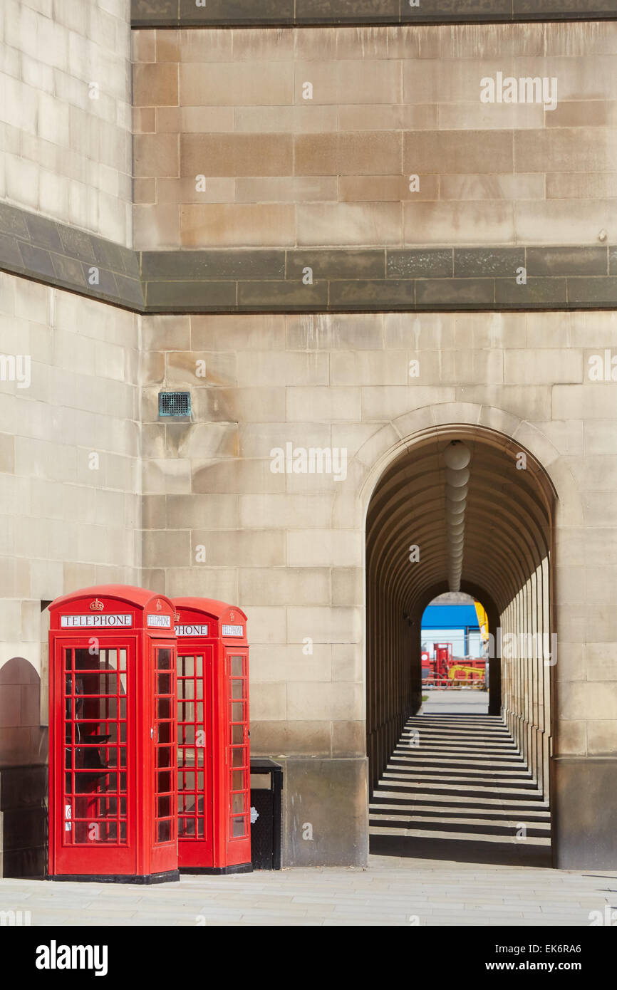 Manchester Town Hall extension arches walkway with red telephone boxes - Stock Image