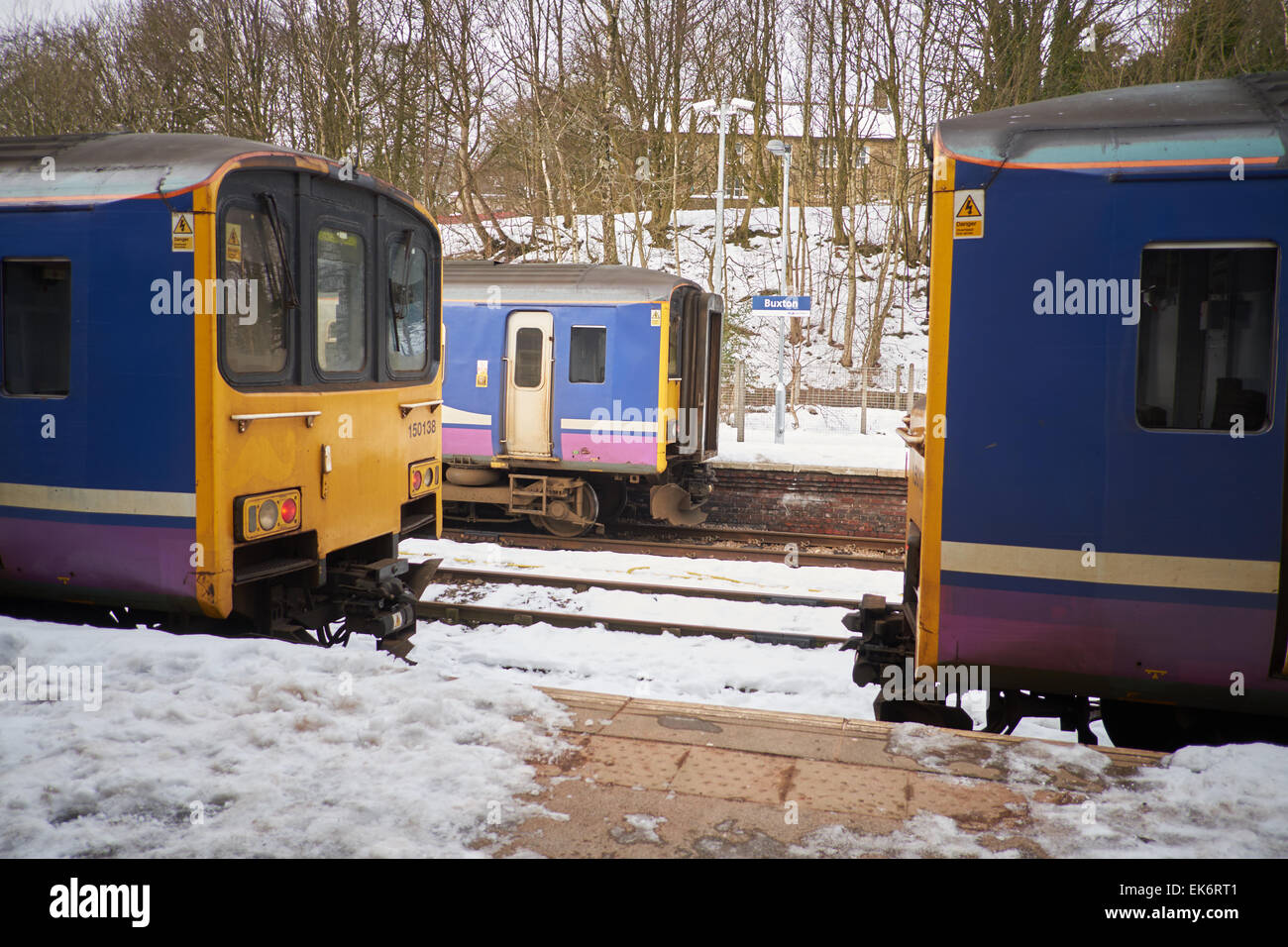 Buxton is a spa town in Derbyshire, England UK Northern Rail units wait in the snow at the train station terminus - Stock Image