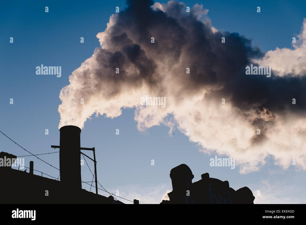 Electrical power industrial smoking chimney, steam against clear sky Stock Photo