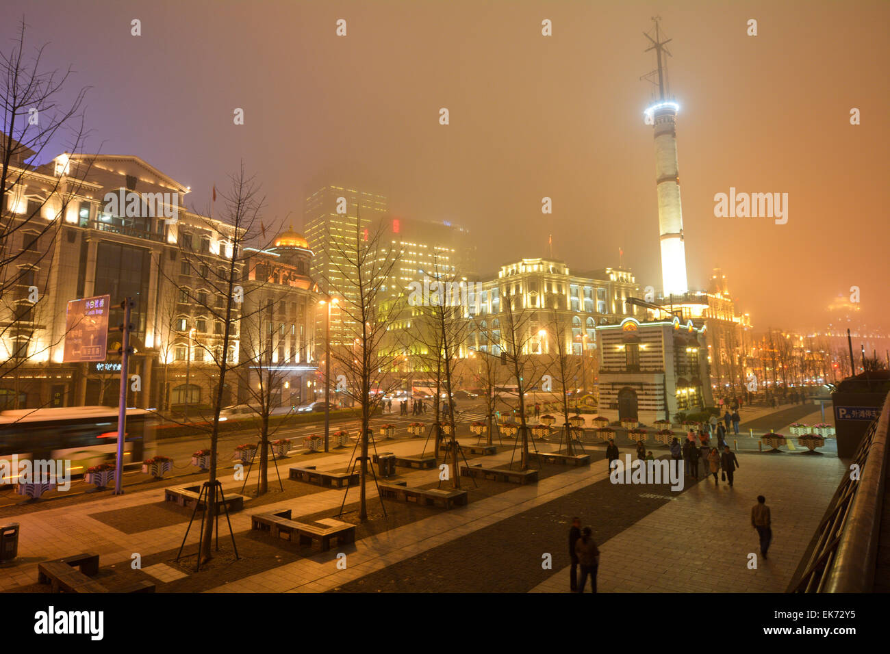 SHANGHAI, CN - MAR 16 2015:Visitors on Shanghai - The Bund or Waitan on foggy night.Shanghai Bund has dozens of historical buildings and It is one of the most famous tourist destinations in Shanghai. Stock Photo