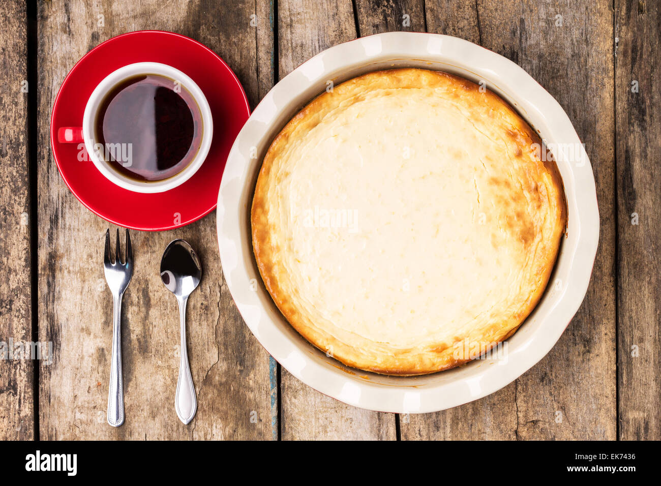 Fresh baked cheesecake with cup of black tea on wooden table. Top view image of breakfast eating background Stock Photo