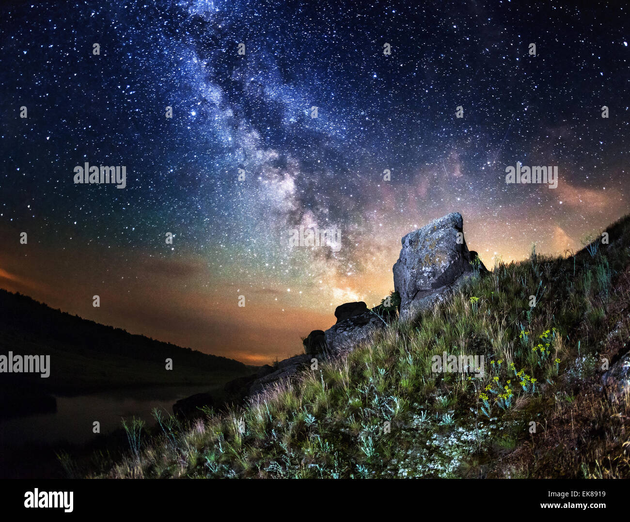 Milky Way. Beautiful summer night sky with stars, rocks, trail and green plants in Ukraine - Stock Image
