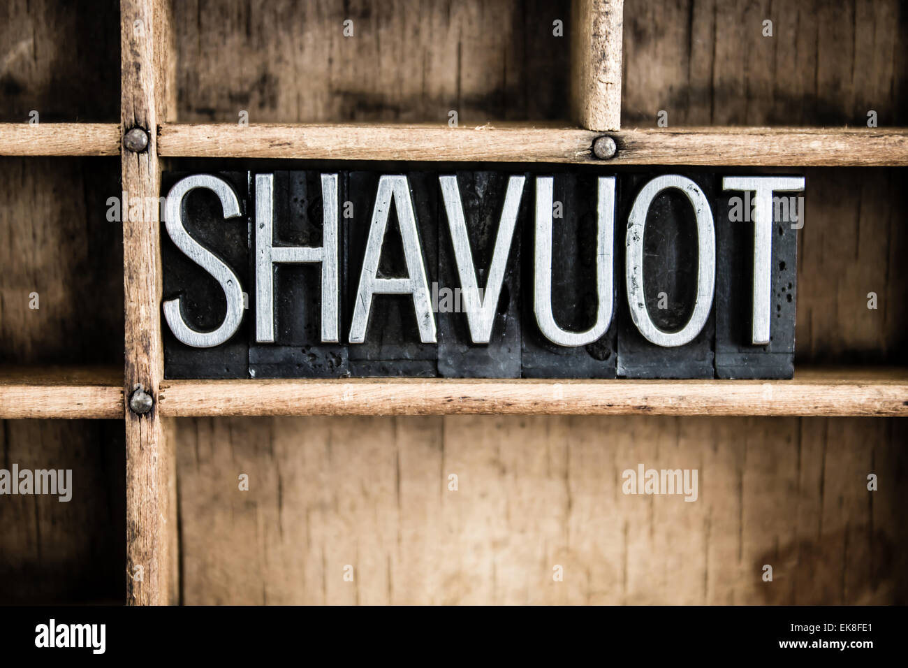 The word 'SHAVUOT' written in vintage metal letterpress type in a wooden drawer with dividers. - Stock Image