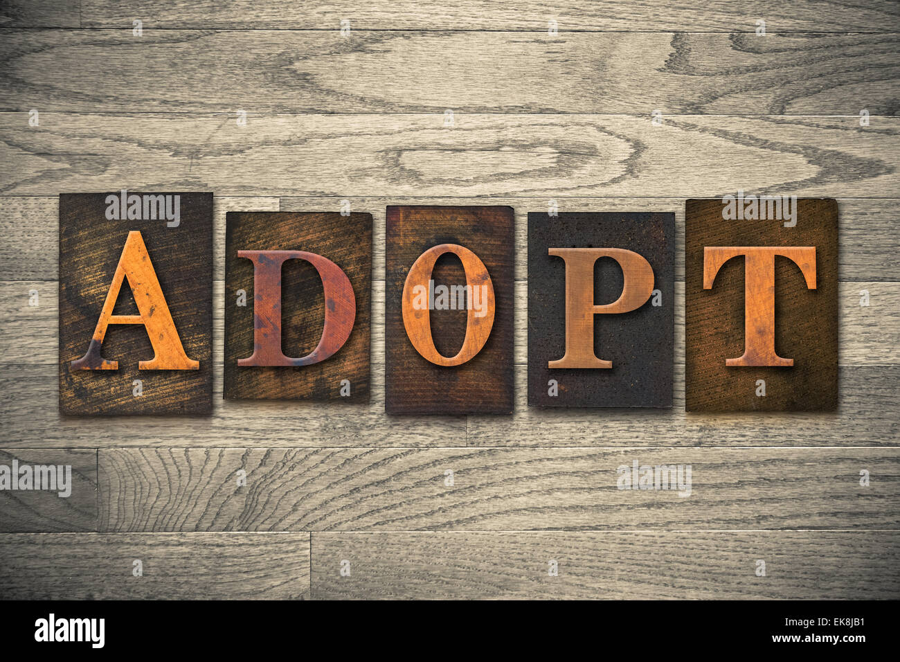 "The word ""ADOPT"" theme written in vintage, ink stained, wooden letterpress type on a wood grained background."" theme Stock Photo"