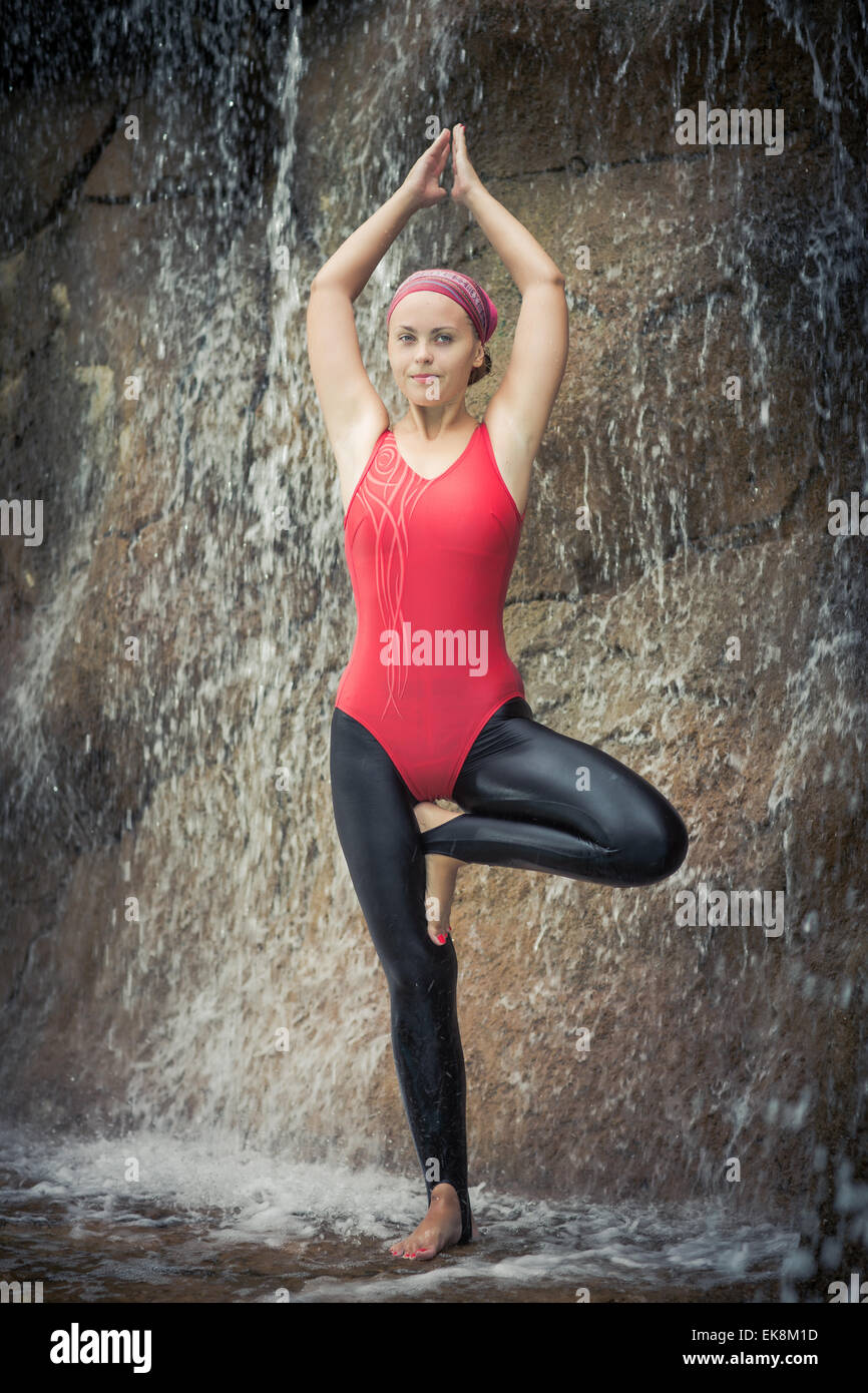 Woman practicing yoga near waterfall. Tree Pose. Vriksasana Stock Photo