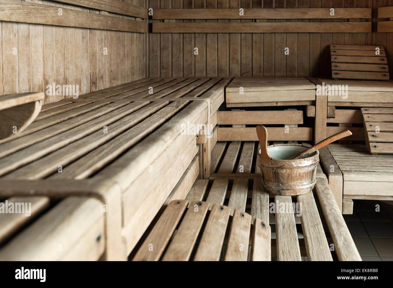 Spa wooden sauna interior with water bucket. - Stock Image