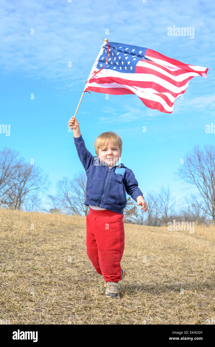 Young child waves the American flag - Stock Image