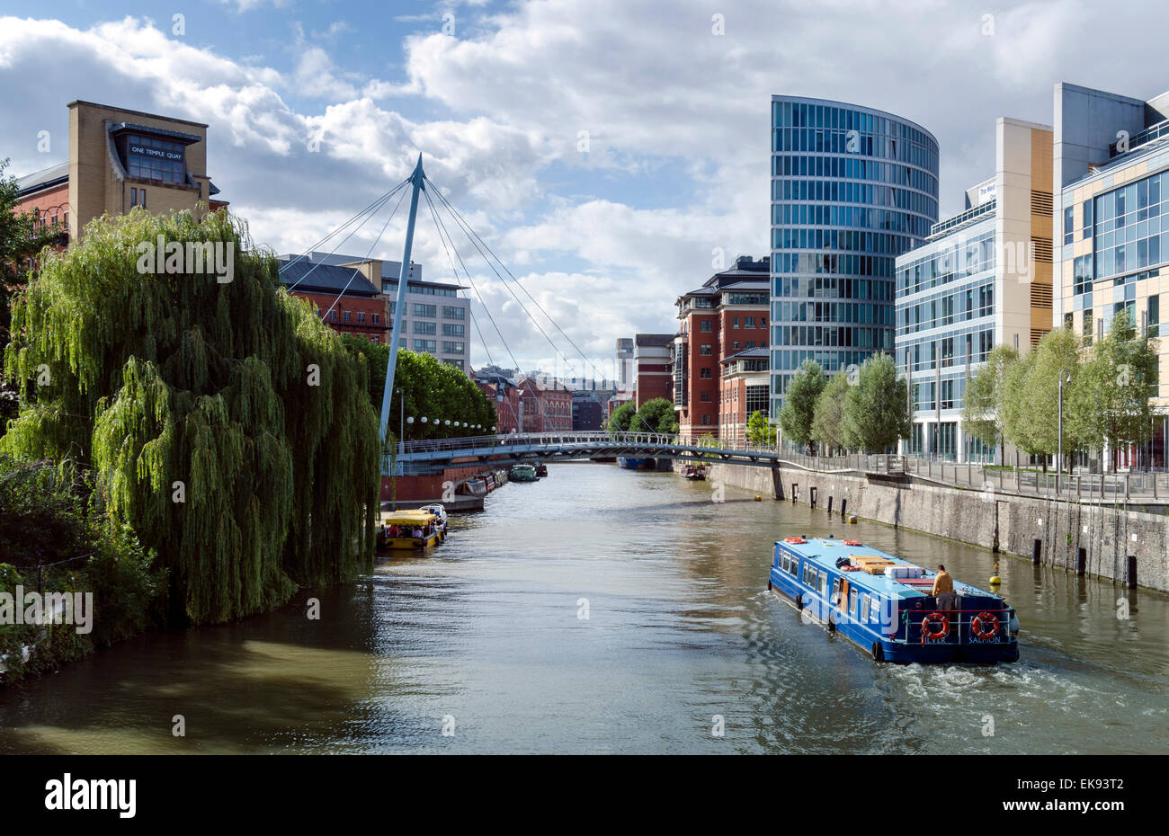 A boat passing under Valentine's Bridge in the Temple Quay area of Bristol, with its mix of old and modern architecture. - Stock Image