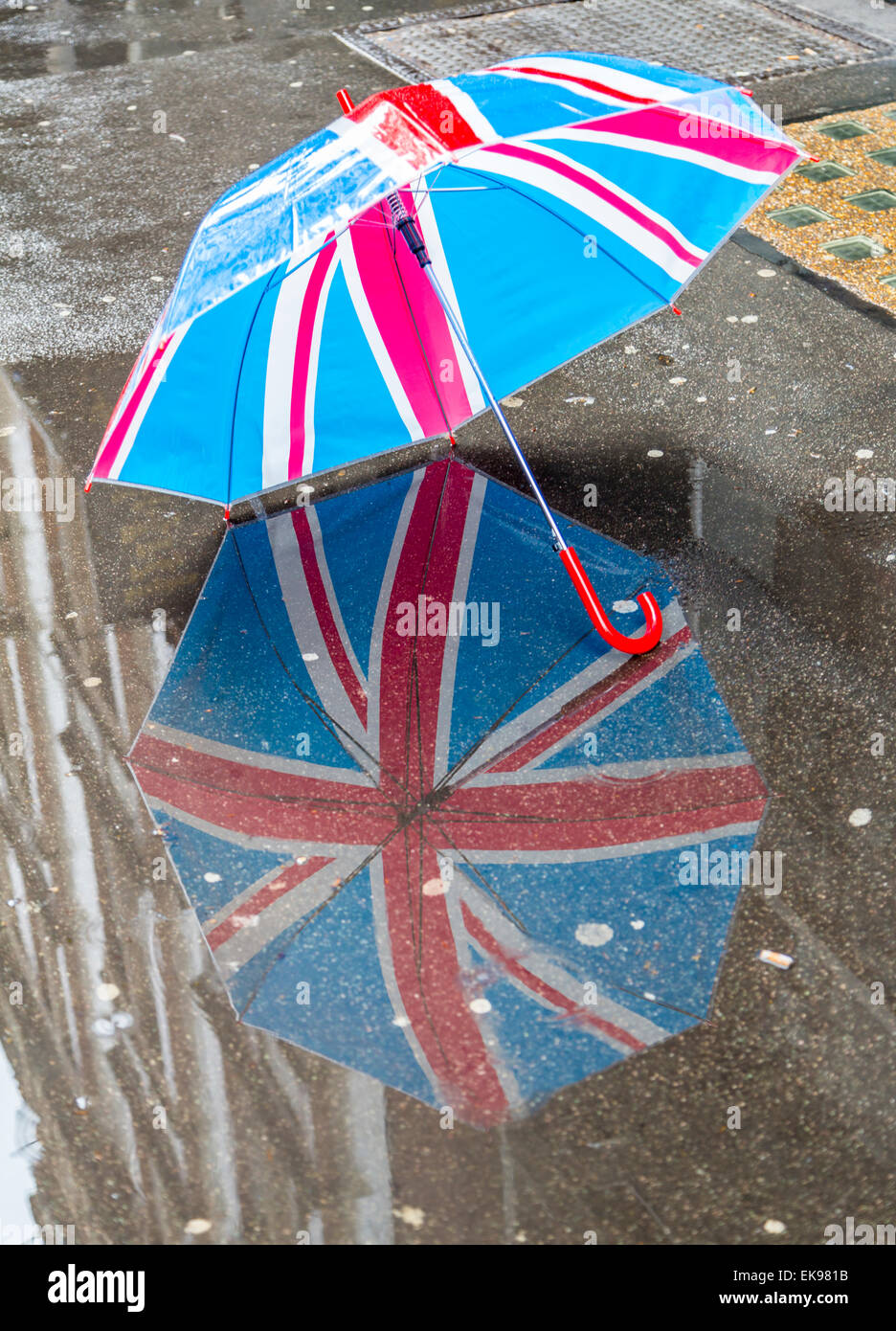 A Union Jack umbrella reflection in a puddle in a raining London Street - Stock Image