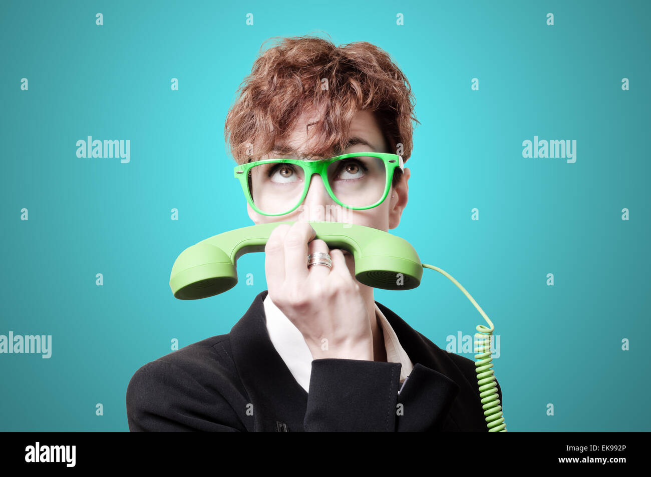 business woman with green phone handset like mustache - Stock Image