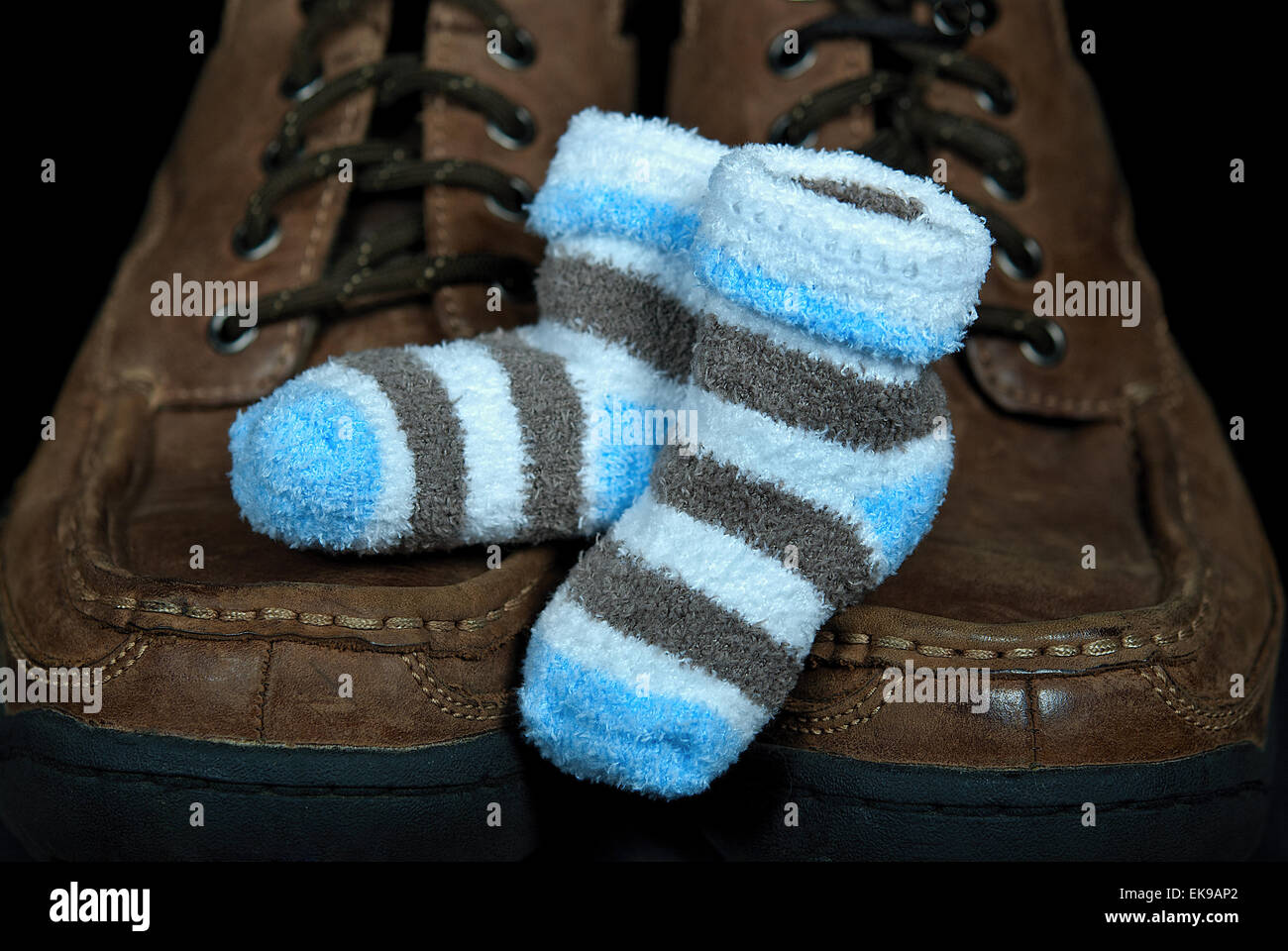 boy baby booties on adult men's shoes - Stock Image