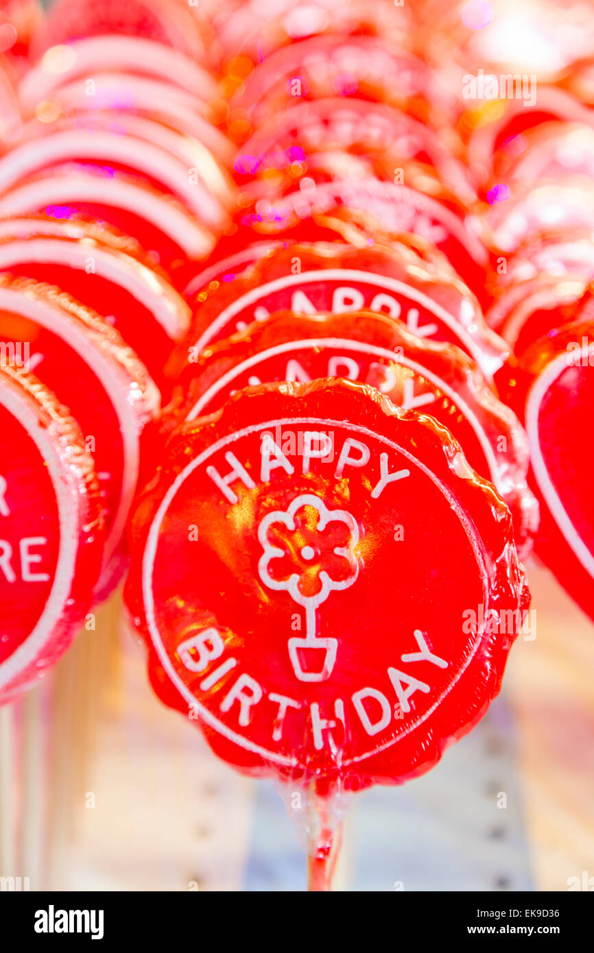 An image of a row of Happy Birthday lollipops on sticks in bright red - Stock Image