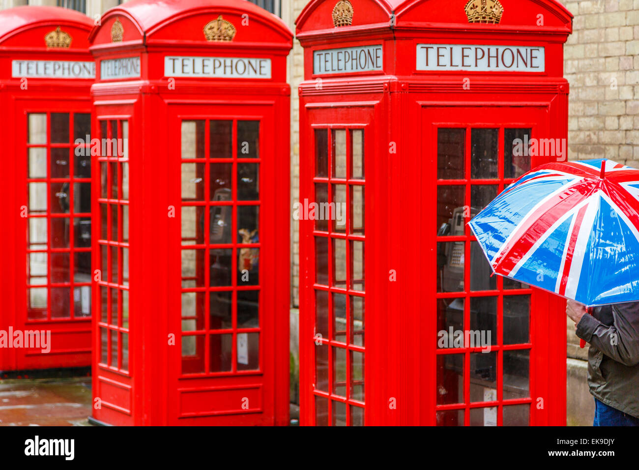 London Telephone boxes in the rain with a person holding a Union Jack Umbrella - Stock Image