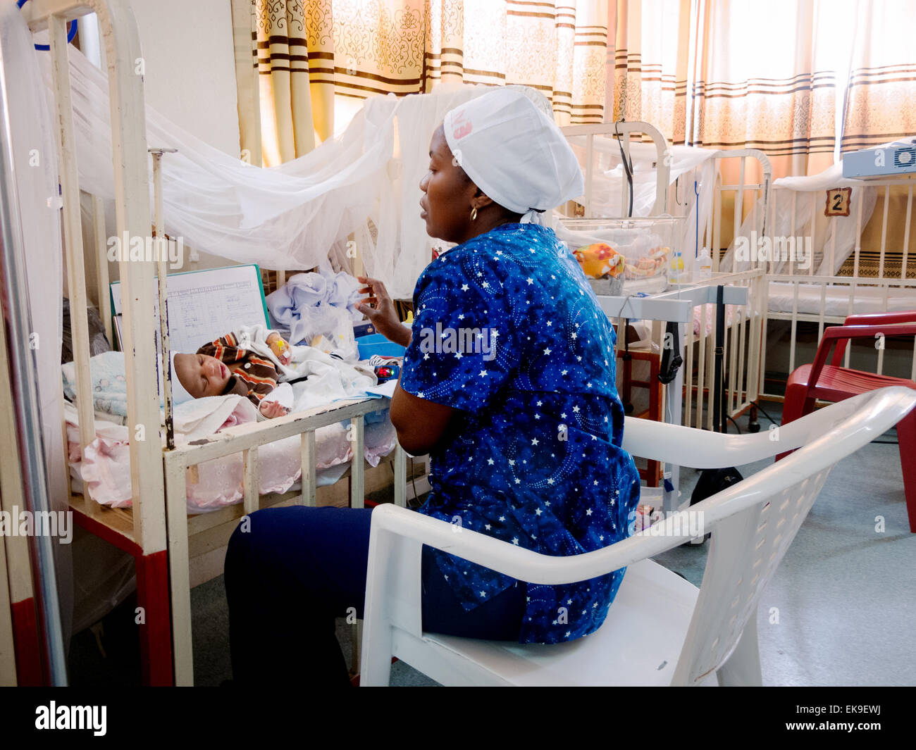 An African nurse nursing a baby in a ward; The Heal Africa charity hospital, Goma, Democratic Republic of Congo - Stock Image