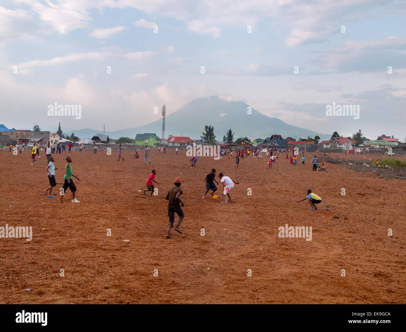 African children playing football; Goma, with the volcano Mount Nyriagongo, Democratic republic of Congo ( DRC ), - Stock Image