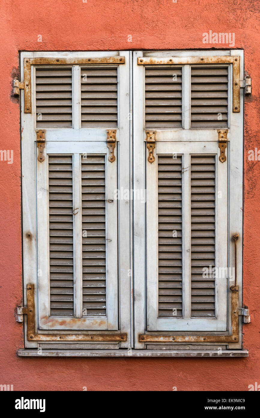 White Weathered French Wooden Window Shutters On A Red Wall