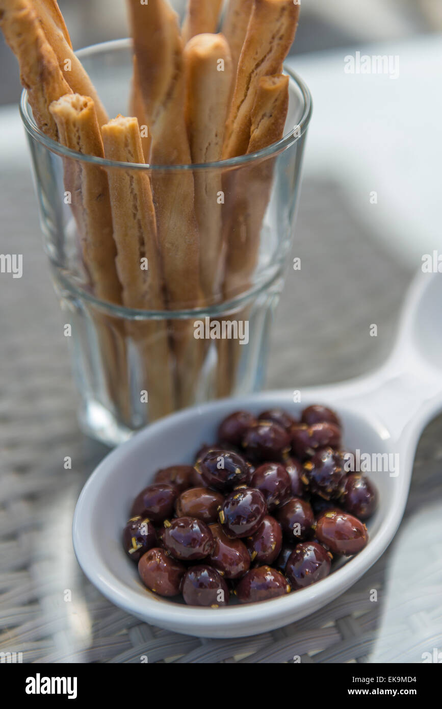 Small black olives in a bowl with breadsticks in a glass tumbler on a table at a bar or restaurant - Stock Image