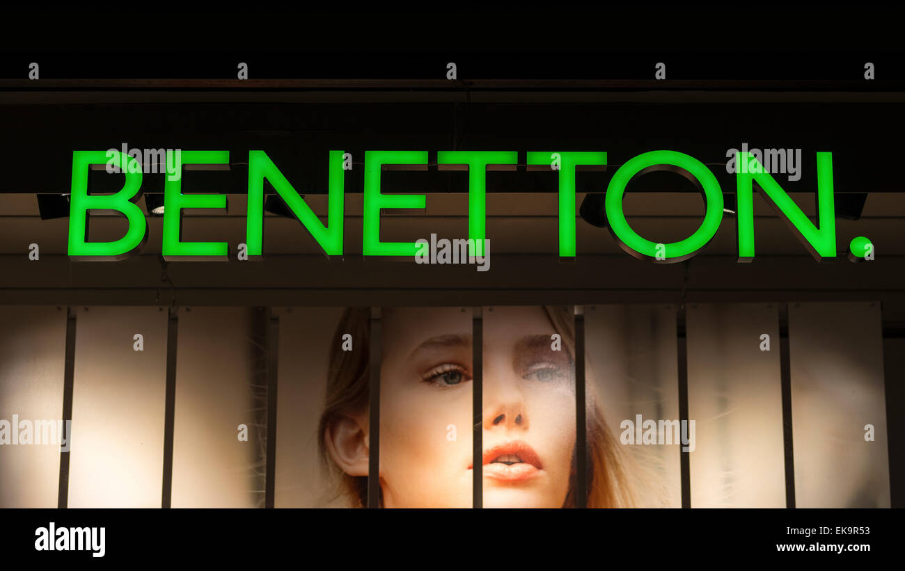 A green illuminated Benetton shop sign at night above a window display background of the photo of a female model - Stock Image