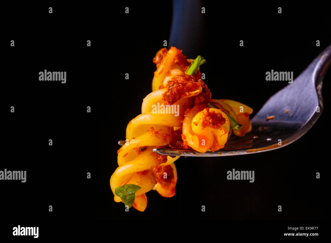 A close up image of steaming hot Fusilli Pasta  on a fork against a black background - Stock Image