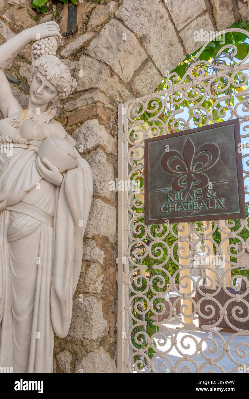 The gate into the gardens of the Chevre d'Or hotel in Eze, France with a statue and the Relais & Chateaux - Stock Image