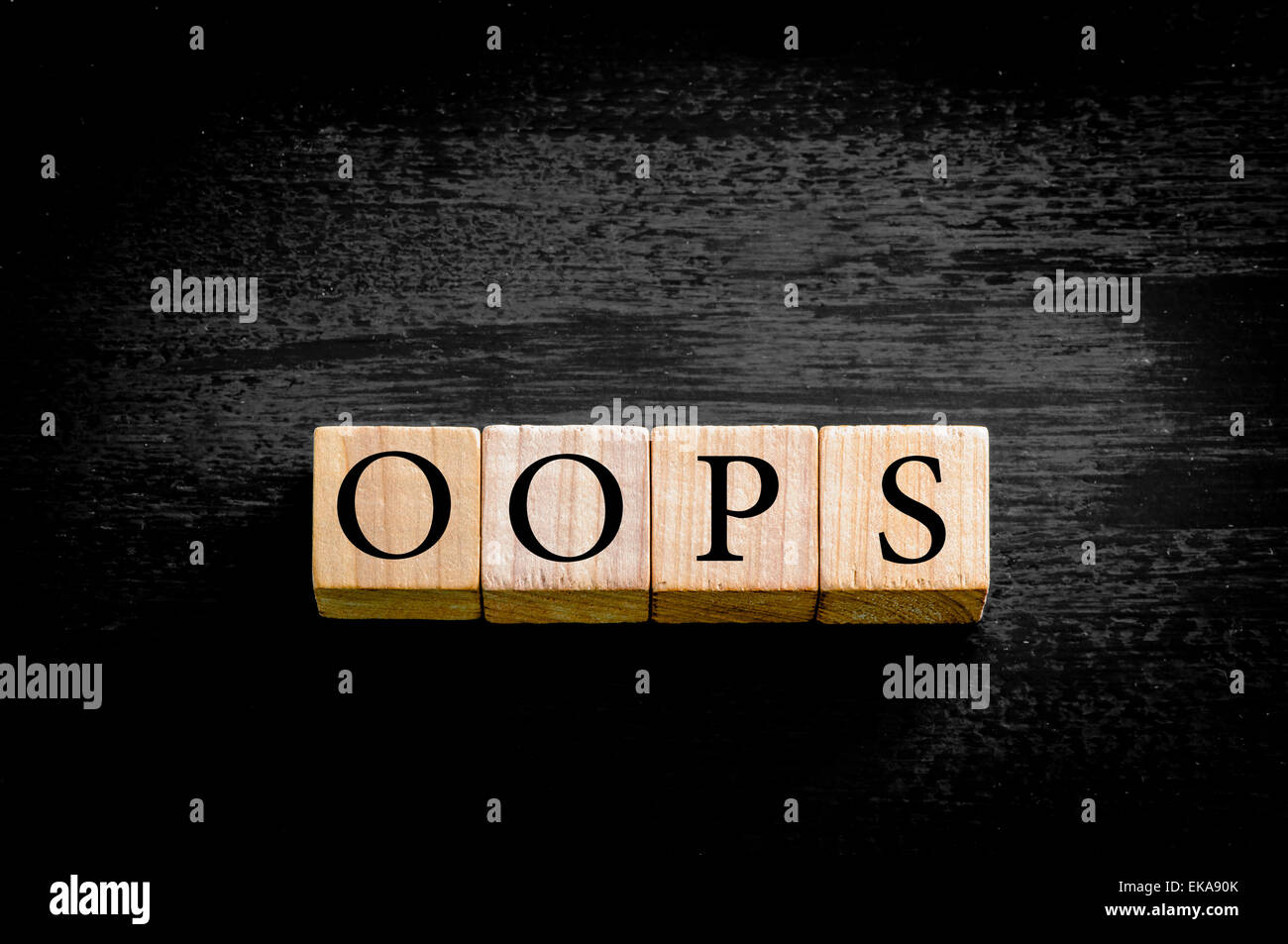 Word OOPS. Wooden small cubes with letters isolated on black background with copy space available. Concept image. - Stock Image