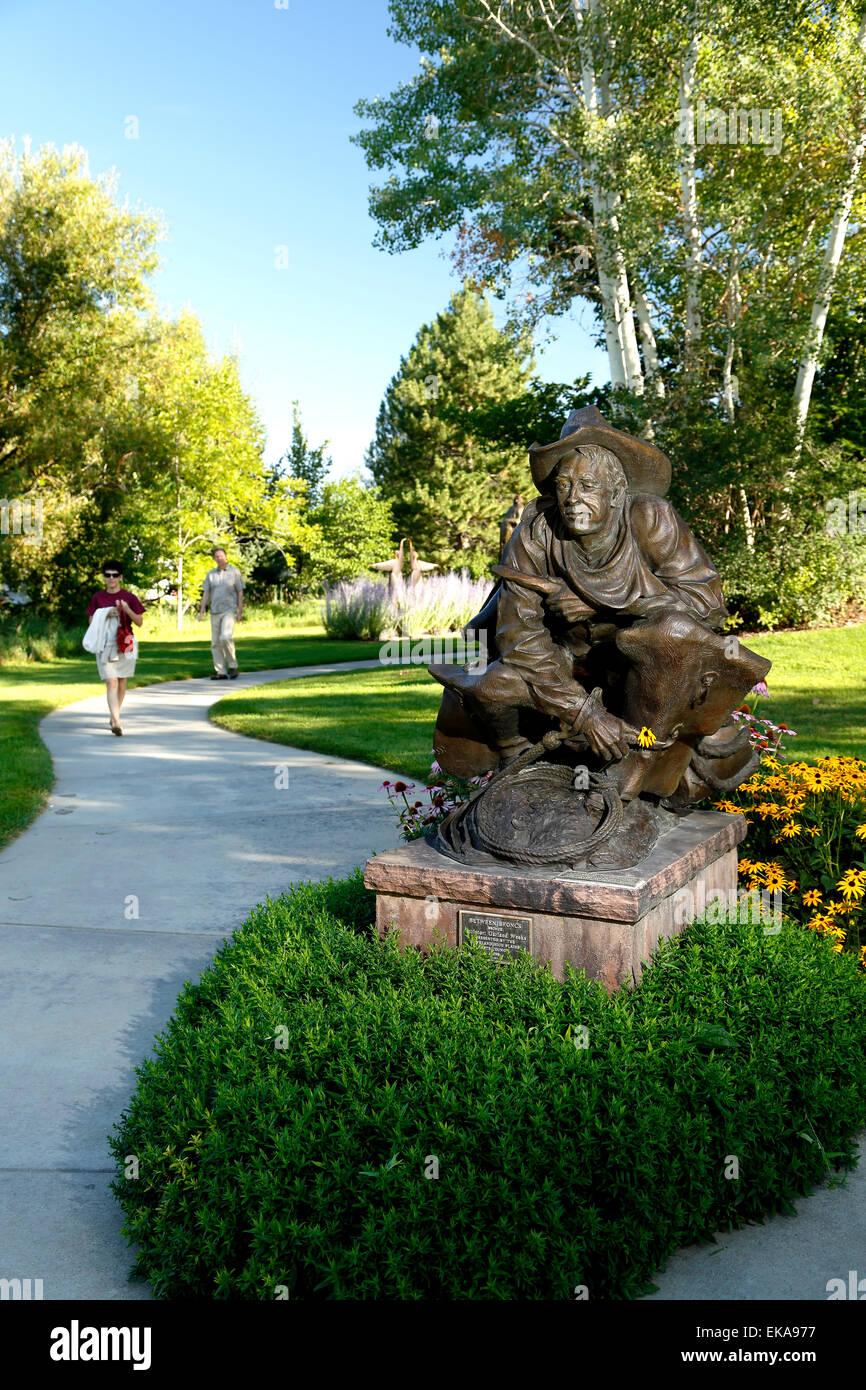 'Between Broncs' sculpture, by Garland Weeks, and walkers on trail, Benson Sculpture Garden, Loveland, Colorado - Stock Image