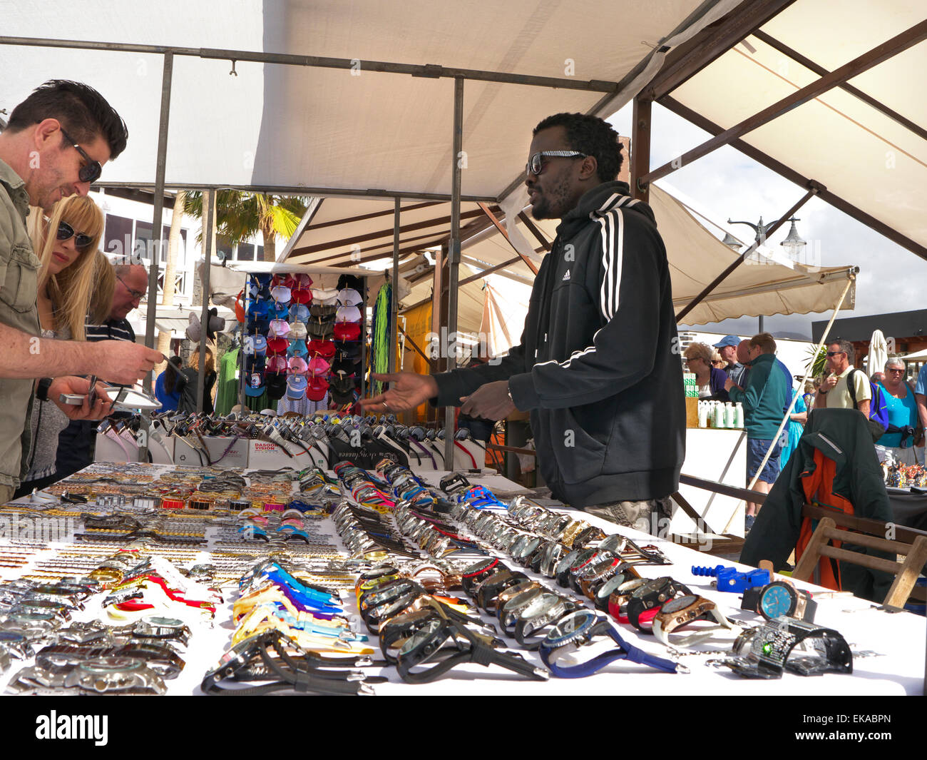 North African gentleman market stallholder selling inexpensive watches to tourists branded with luxury names including - Stock Image