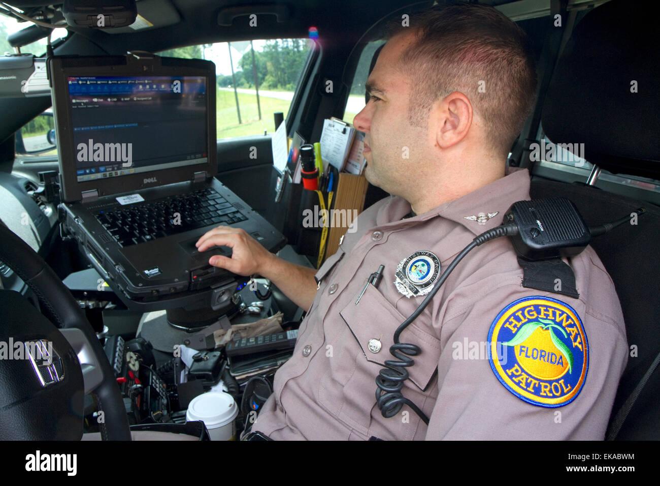 Florida state trooper using computer in patrol car. - Stock Image