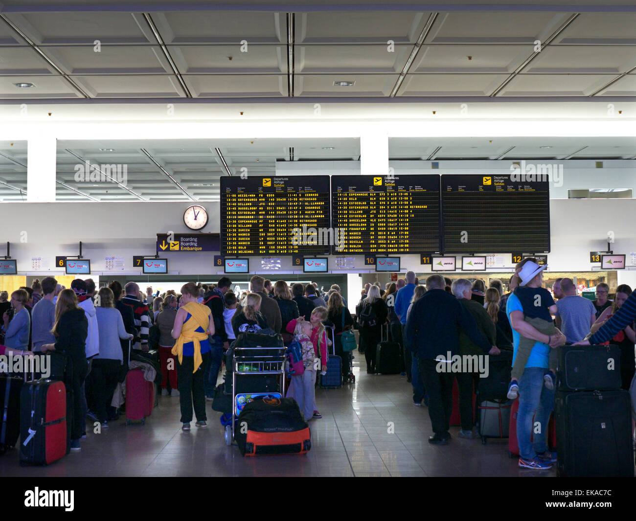 Delayed queues of charter flight passengers and luggage wait on airport concourse to check in to their flights - Stock Image