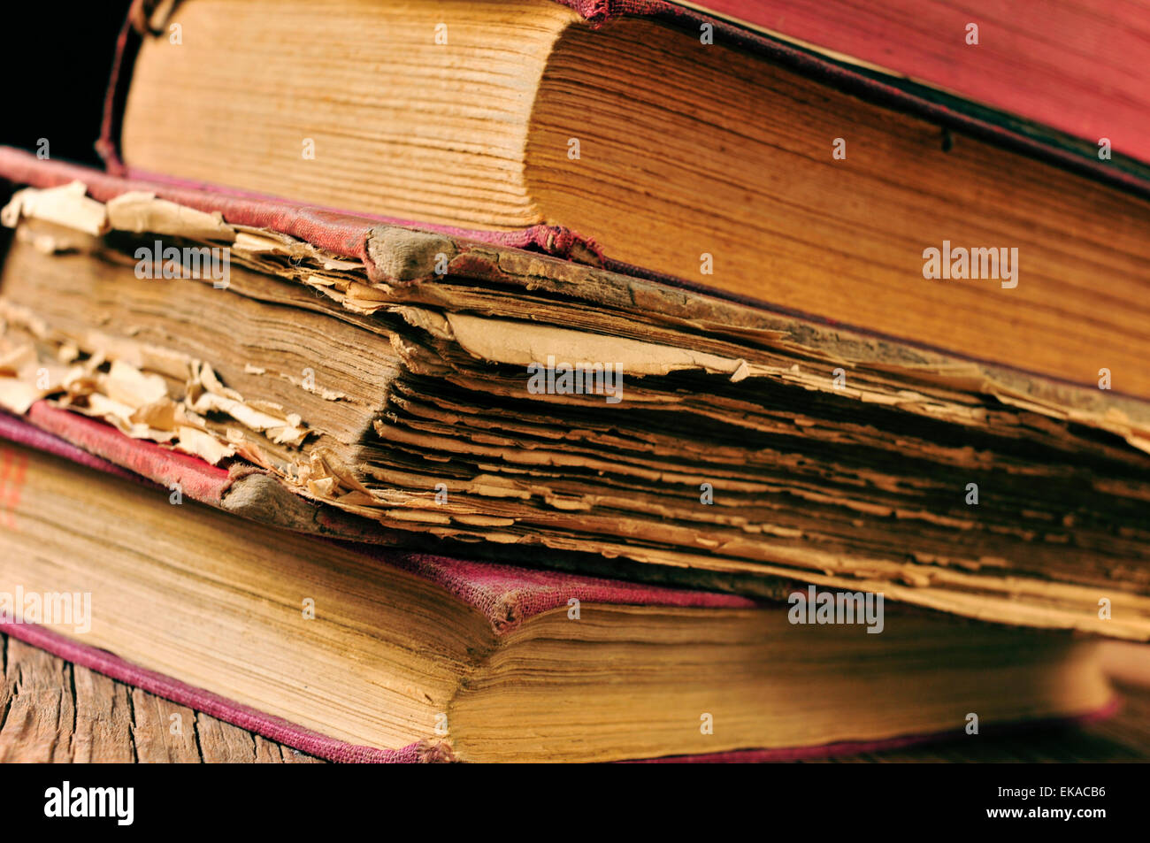 closeup of a pile of worn-out old books on a rustic wooden table - Stock Image