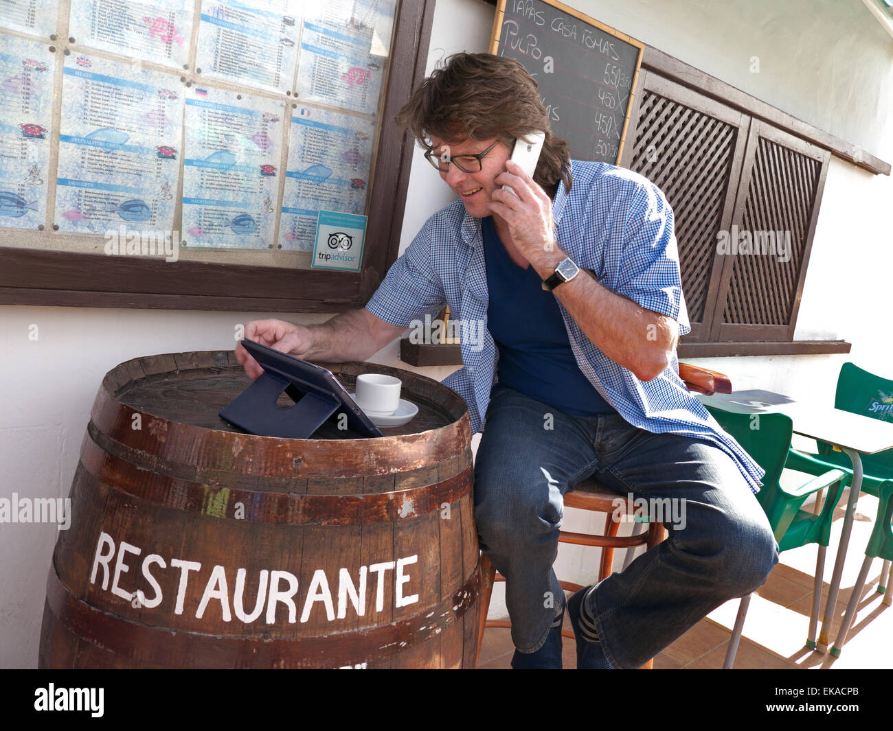 Mature man using his iPhone 6 and iPad Air tablet computer abroad at alfresco Spanish restaurant bar Stock Photo