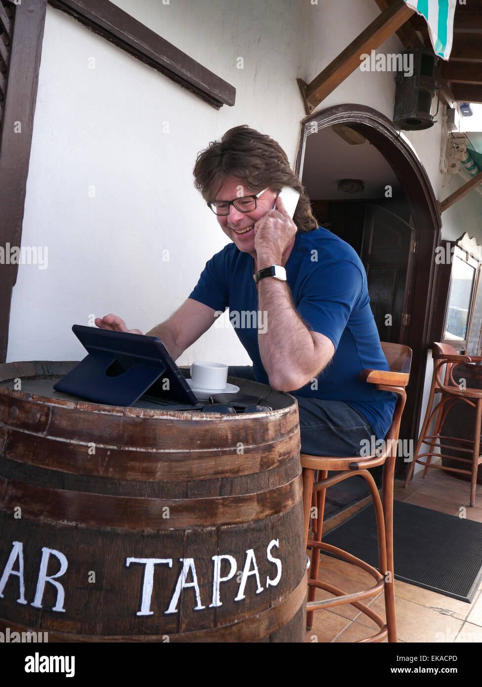 Man using his iPhone 6 and iPad Air tablet computer abroad at alfresco Spanish Tapas restaurant bar - Stock Image