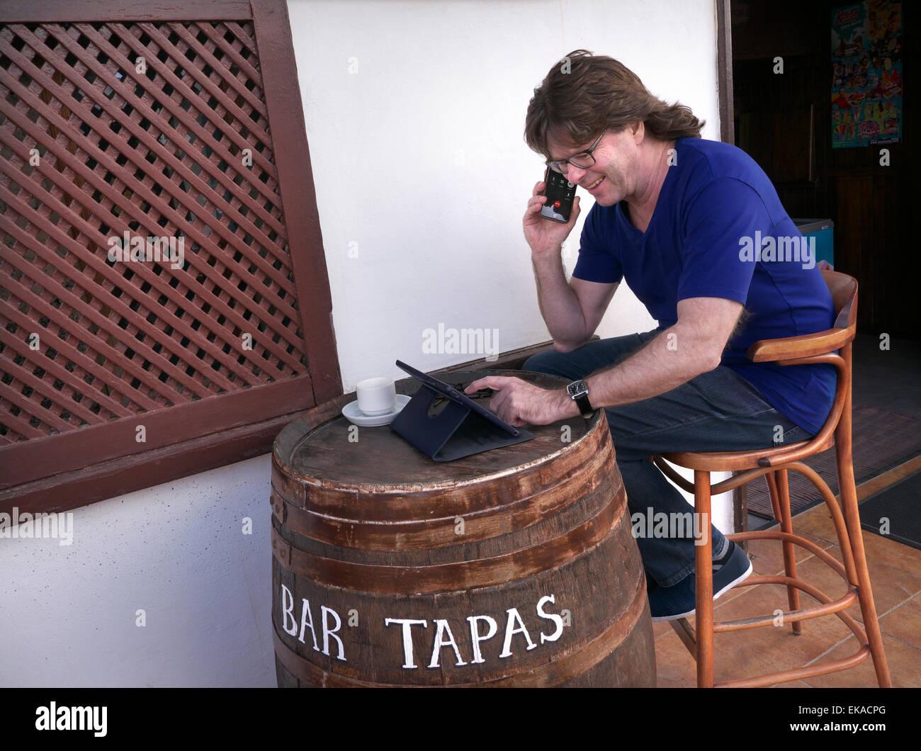 Man roaming with his iPhone 6 and iPad Air tablet computer abroad at alfresco Spanish Tapas restaurant bar - Stock Image