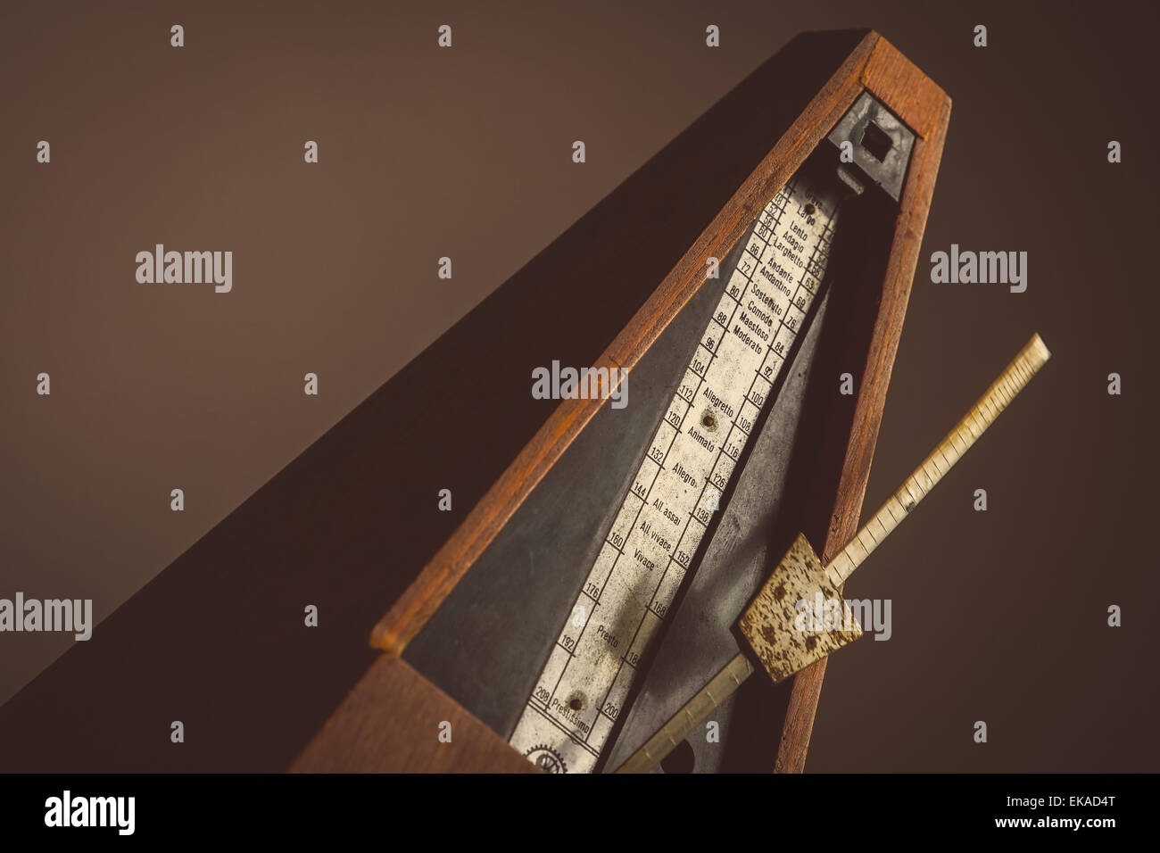 Color shot of a vintage metronome, on a black background. - Stock Image