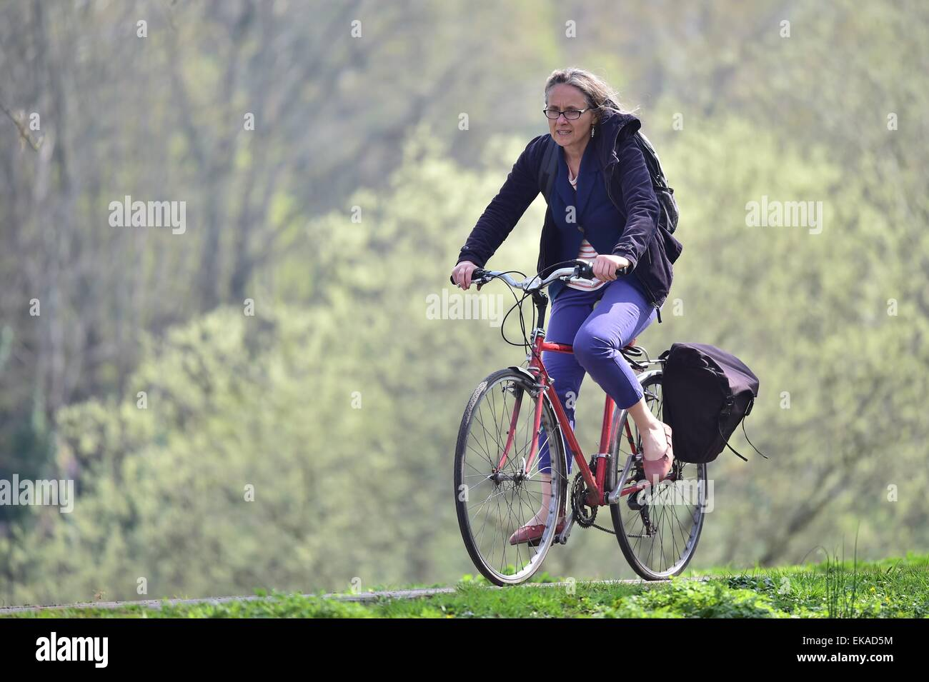 Female cyclist rides bike on the Taff Trail in Cardiff, South Wales, during warm sunny weather. - Stock Image